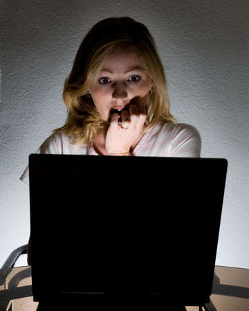 Frightened woman looking at the computer screen in the dark with the light coming from the computer Stock Photo - 948198