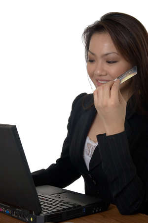 Attractive young asian woman in business attire sitting in front of a laptop computer holding onto a credit card Stock Photo - 958243