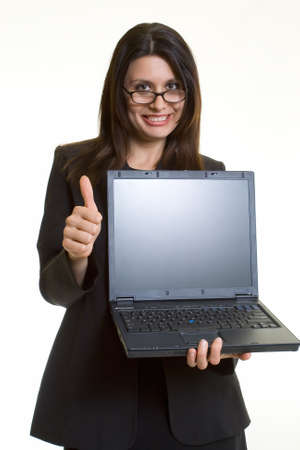 Attractive brunette smiling business woman holding up an open laptop computer showing the blank front screen holding thumb up standing on white photo