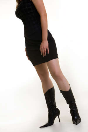 Attractive body of woman wearing black mini skirt and sexy black boots standing on white background photo