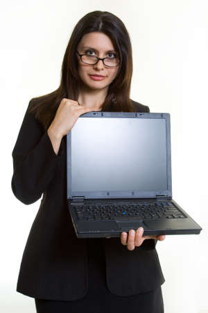 Attractive brunette smiling business woman holding up an open laptop computer showing the blank front screen standing on white