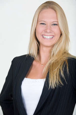 Attractive blond woman dressed in professional business suit with laughing expression