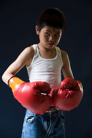 Young asian boy with mean expression wearing red boxing gloves standing on black background