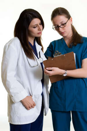 Two woman healthcare workers one wearing a doctors lab coat holding a chart the other in scrubs standing on white Stock Photo - 999141