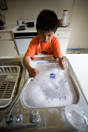 Young independent asian boy wearing an apron standing in front of kitchen sink full of soapy water washing the dishes