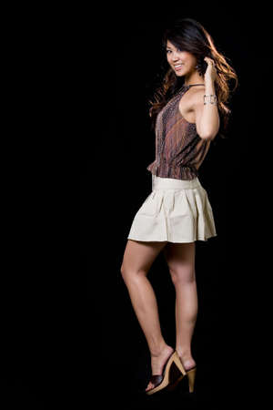 Full body of beautiful brunette Asian woman wearing mini skirt with blowing backlit hair on black