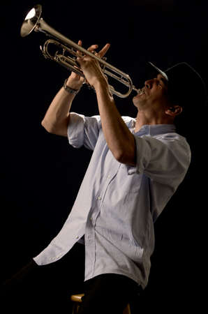 Handsome young man playing a trumpet wearing a black hat on black