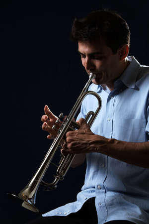 Handsome young man playing a trumpet wearing blue shirt on black background Stok Fotoğraf