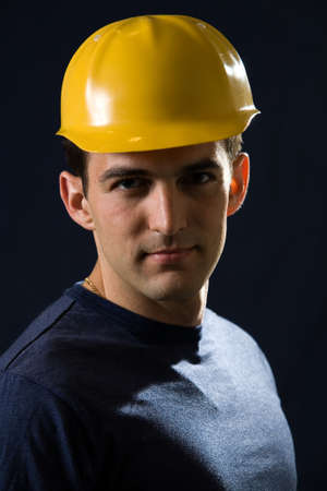 hard: Handsome brunette young man wearing a yellow hard hat and navy blue tshirt standing on black background