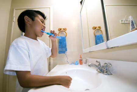 Little asian boy at home in bathroom looking in mirror while brushing his teeth Banque d'images