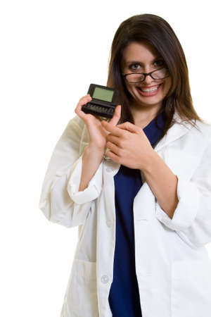pager: Woman doctor in glasses wearing a doctors lab coat holding up and pointing to an open pager showing blank screen standing on white Stock Photo