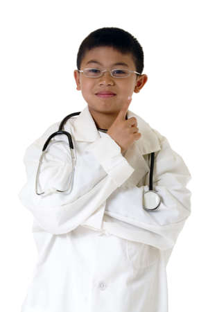 Little asian boy wearing doctor coat and eyeglasses with a stethoscope around shoulders standing on white background