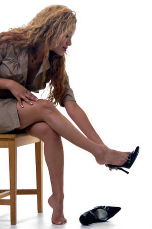 Attractive blond woman sitting on wooden chair removing black high heel shoes Stock Photo