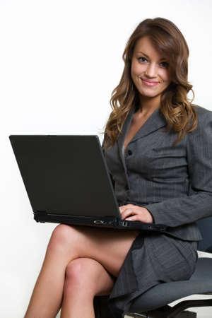ラップトップ コンピューターでタイプしている間ビジネス スーツを着て椅子に座って、ブルネットの魅力的な笑顔ビジネス女性 写真素材