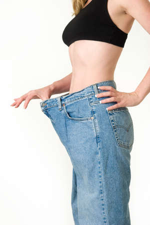Woman demonstrating weight loss by wearing an old pair of jeans and holding out to show how big the pants are
