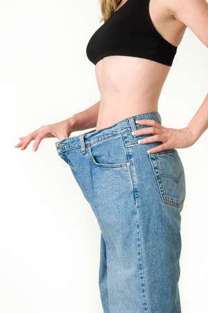 Mujer que demuestra la pérdida de peso con el uso de un viejo par de pantalones vaqueros y la celebración a cabo para mostrar cuán grande son los pantalones  Foto de archivo - 1193728