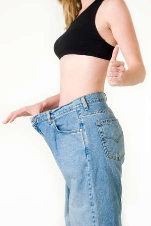 obtain: Woman demonstrating weight loss by wearing an old pair of jeans and holding out to show how big the pants are and holding up thumb to show success