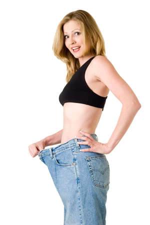 Attractive slim blond woman demonstrating weight loss by wearing an old pair of jeans and holding out to show how big the pants are Stock Photo - 1214995