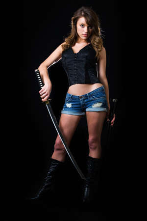 Attractive sexy woman in shorts holding a samurai sword standing on black Фото со стока