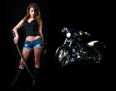 Attractive sexy woman in shorts holding a samurai sword standing beside a harley motorcycle on black Stock Photo