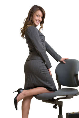 Attractive intelligent looking woman kneeling on an office chair wearing professional grey colored business suit on white