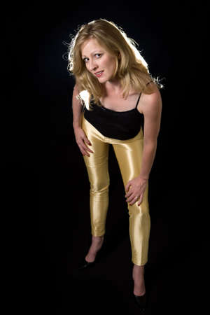 tight fitting: Full body of a beautiful blond hair woman wearing sexy tight leather yellow pants and black top posing on black background Stock Photo