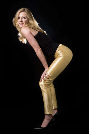 tight fit: Full body of a beautiful blond hair woman wearing sexy tight leather yellow pants and black top posing on black background Stock Photo