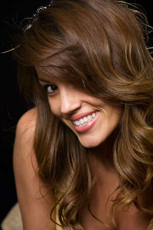 leaning forward: Close up of beautiful brunette woman leaning forward smiling on black Stock Photo
