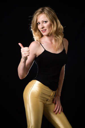 Full body of a beautiful blond hair woman wearing sexy tight leather yellow pants and black top holding up thumb like hitch hiking posing on black background Stock Photo