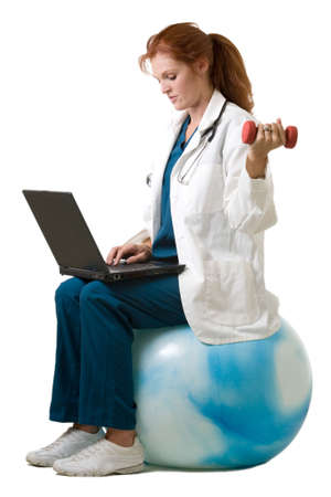 hand weight: Female attractive red haired doctor wearing white lab coat sitting on an exercise ball using a hand weight and typing on a laptop computer Stock Photo