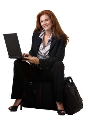 Full body of an attractive red hair woman sitting on a suitcase and typing on a laptop on white
