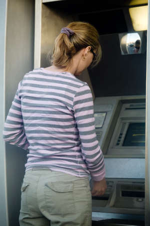 necessity: Woman outside using an automated bank machine