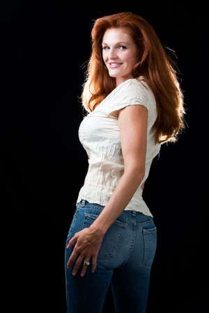 Attractive red hair woman wearing casual clothing standing on black background 免版税图像