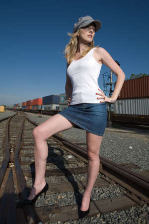 Attractive blond woman standing on the railway tracks with a train behind her wearing engineer hat and white top and mini skirt with sexy long legs