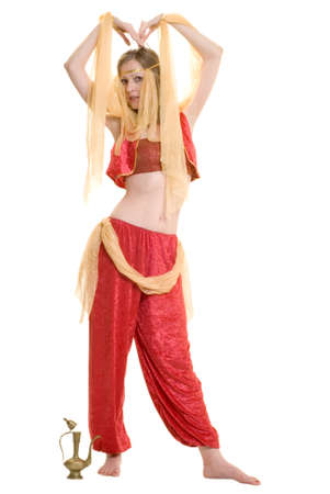 Attractive woman wearing a Genie costume standing in front of a brass lamp on white Stock Photo
