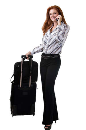 Full body of an attractive red hair woman holding a suitcase on roller wheels and talking on a cell phone standing on white Stock Photo