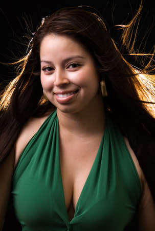 wind blown hair: beautiful brown hair woman wearing green dress with wind blown hair on black background with rim light