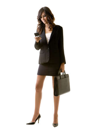Full body of tall young brunette woman in professional business suit standing on white holding a briefcase and a cell phone 스톡 콘텐츠