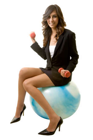 Attractive brunette smiling business woman sitting on a blue workout ball holding weights wearing black business suit on white Stock Photo