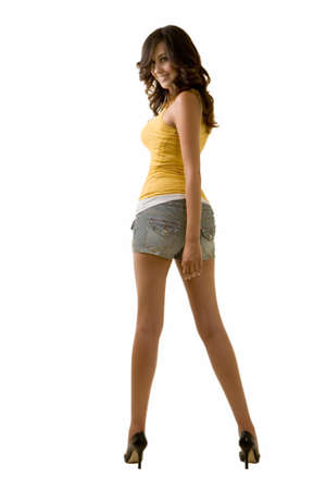 long sexy legs: Full body of an attractive tall brunette woman with long sexy legs wearing shorts and yellow tank top looking back over shoulder standing on white background Stock Photo