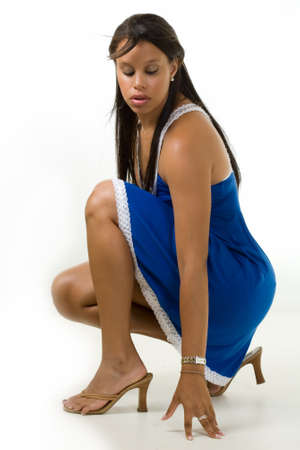 Beautiful brunette young African American mixed race woman wearing blue dress crouching on the floor with eyes looking down 写真素材