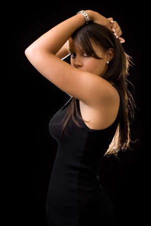 Beautiful brunette young African American woman wearing black top posing with arm on head on black Banco de Imagens