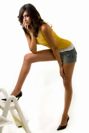 Full body of an attractive tall brunette woman with long sexy legs wearing shorts and yellow tank top with one foot up on a step ladder on white background