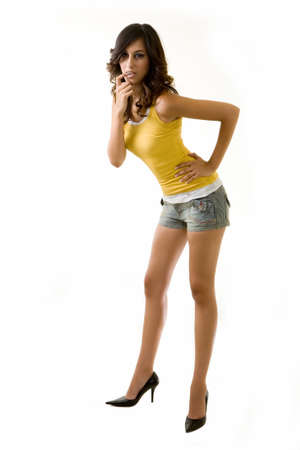 Full body of an attractive tall brunette woman with long sexy legs wearing shorts and yellow tank top bending while standing on white background photo