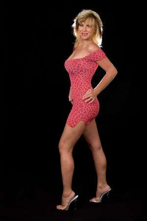 donne mature sexy: Completo di un corpo capelli biondi donna che indossa abito corto rosa posa sexy su sfondo nero Archivio Fotografico