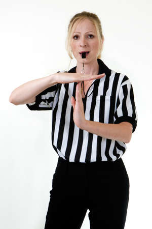 foul: Attractive blonde woman wearing black and white striped referee uniform blowing on a whistle making the hand signal for technical foul or time out