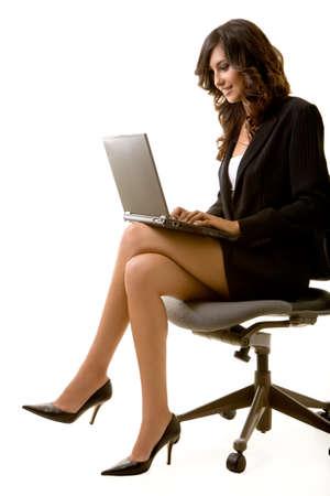 魅力的なブルネットのビジネス女性のラップトップ コンピューターで入力中の黒のビジネス スーツを着て椅子に座って