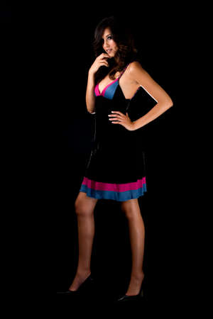 Full body of a beautiful brown hair woman with sexy long legs wearing dress standing on black background photo