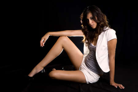 Whole body of a beautiful brown hair woman with sexy long legs wearing white shorts and matching top sitting on the floor on black background photo
