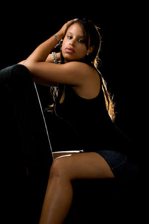 sexy leg: Beautiful young African American woman wearing black dress sitting on black chair over black
